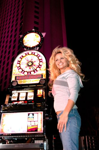 """Pam poses by her new """"Pam Anderson"""" slot machine"""